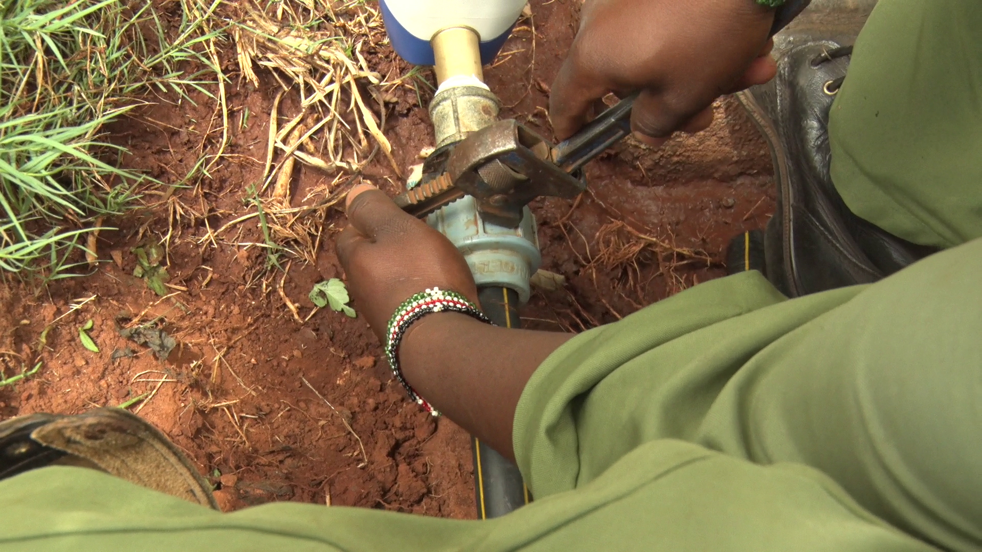 A technician connecting the smart water meter to a water pipe in Embu.